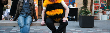 sitting next to a man dressed as a bee